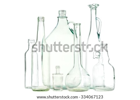 Group of mixed clear colorless glass bottles or glass waste on white