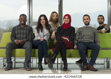Group of mixed-race students are hanging out and talking in university hall - stock photo