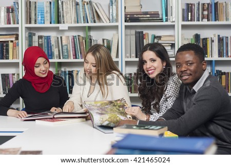 Group of mixed-race students studying at university library for exams - stock photo