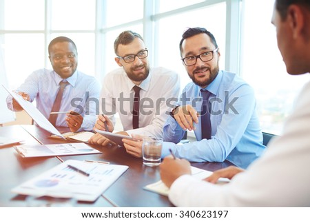 Group of modern employees looking at their colleague during discussion