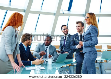 Group of modern multi-ethnic employees sharing and discussing their ideas at meeting - stock photo