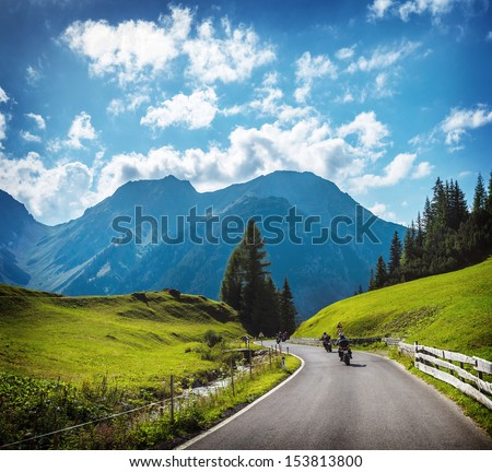 Group of motorbikers in the mountains, race on mountainous highway, beautiful landscape, trip along Alps, travel and tourism concept - stock photo