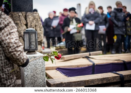 Group of mourners staying by the opened grave at a cemetery during a funeral ceremony - stock photo