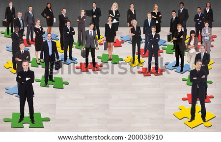 Group of multi ethnic business people standing on jigsaw pieces - stock photo