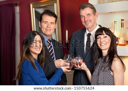 Group of multi- ethnic friends celebrating toasting each other with flutes of champagne and smiling at the camera.