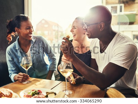 Group of multi ethnic friends drinking wine at a cafe outside - stock photo