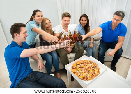 Group Of Multi-ethnic Friends Enjoying Pizza And Beer In Party - stock photo