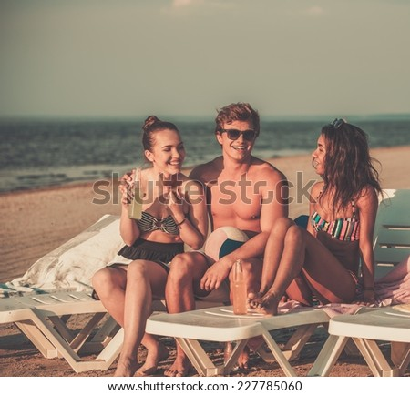 Group of multi ethnic friends sunbathing on a deck chairs on a beach  - stock photo