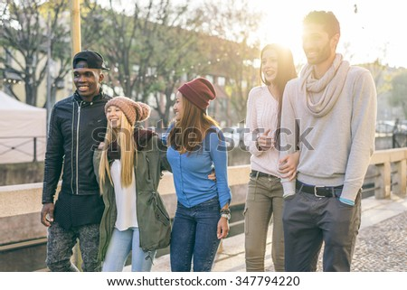 Group of multi-ethnic friends walking on the streets and smiling - Young people having fun outdoors - stock photo