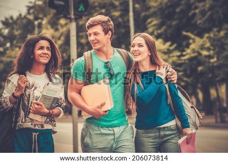 Group of multi ethnic students walking in a city  - stock photo