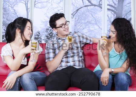 Group of multi ethnic teenagers sitting on sofa while drinking beer, shot at home in winter day - stock photo