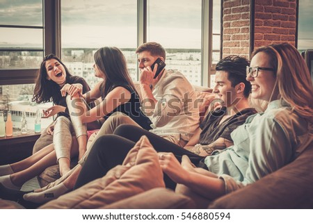Group of multi ethnic young friends having fun in home interior