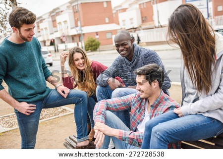 Group of multi-ethnic young people having fun together outdoors in urban background - stock photo