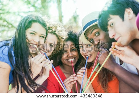 Group of multi race friends enjoying drink outdoor summer party - Multi ethnic students having fun with back lighting - Friendship and party concept - Warm filter with vintage soft desaturated editing - stock photo