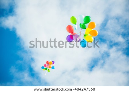 Group of multicolored helium filled balloons in the sky