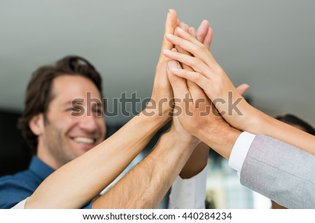 Group of multiethnic businesspeople giving high five. Close up of business hands giving high five in office. Happy business team high fiving in a modern office. - stock photo