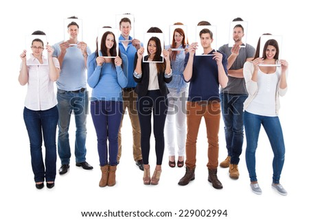Group of multiethnic college students holding photographs in front of faces against white background