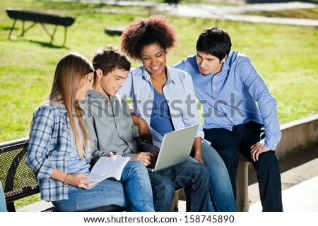 Group of multiethnic college students using laptop in campus