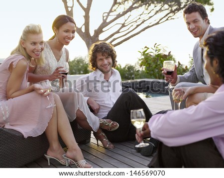 Group of multiethnic friends drinking and socialising on porch - stock photo