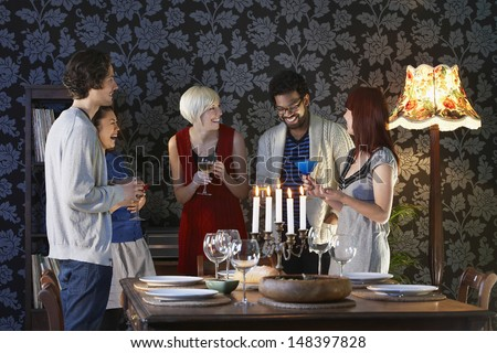 Group of multiethnic friends enjoying drinks by dining table - stock photo