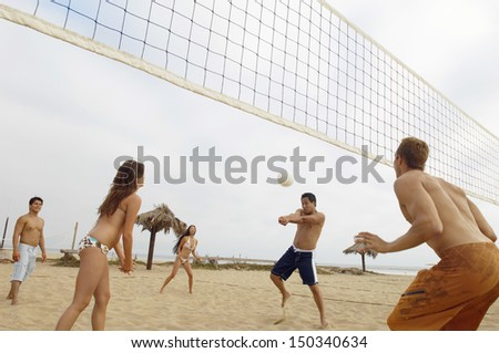 Group of multiethnic friends playing volleyball on beach - stock photo