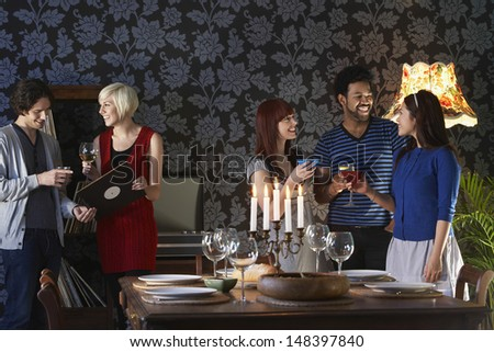 Group of multiethnic friends smiling by dining table - stock photo