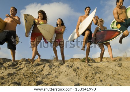 Group of multiethnic friends with surfboards running on sandy beach - stock photo