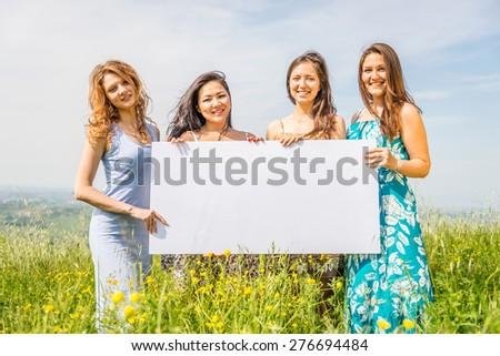 Group of multiethnic girls holding blank advertising board in a flowers field - Four beautiful and happy women promoting something with white billboard - stock photo