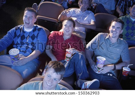 Group of multiethnic male friends watching movie in theater