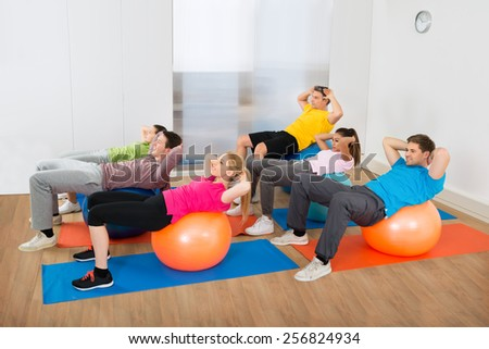 Group Of Multiethnic People Exercising On Pilate Ball At Gym - stock photo