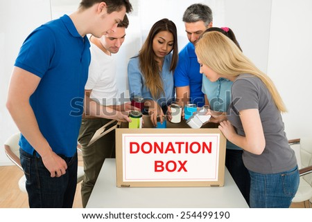 Group Of Multiethnic People Holding Tin Can Looking Inside Donation Box - stock photo