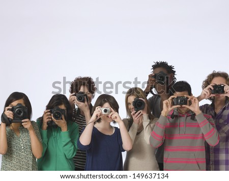 Group of multiethnic people taking photos straight at the camera in studio - stock photo