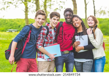 Group of multiethnic teenage students embraced together at park. Two boys and one girl are caucasian, one boy and one girl are black. Friendship, immigration, integration and multicultural concepts. - stock photo