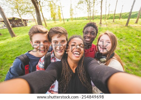 Group of multiethnic teenagers taking a selfie at park. Two boys and one girl are caucasian, one boy and one girl are black. Friendship, immigration, integration and multicultural concepts. - stock photo