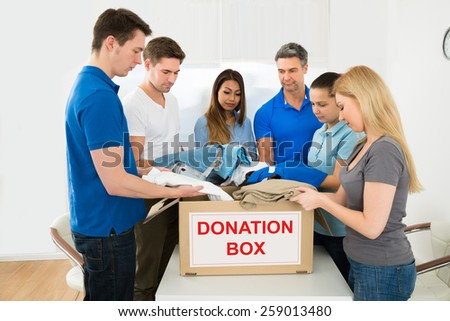 Group Of Multiethnic Volunteers Holding Clothes For Donation - stock photo