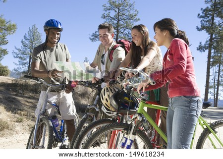 Group of multiethnic young friends with mountain bikes and map - stock photo