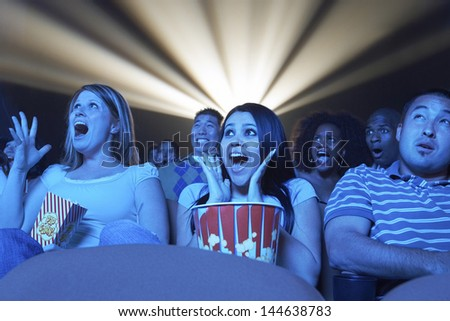 Group of multiethnic young people screaming while watching horror movie in the theatre