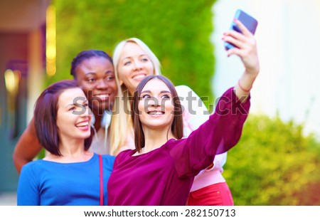 group of multiracial girls taking selfie on smartphone