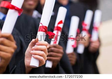group of multiracial graduates holding diploma - stock photo