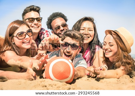 Group of multiracial happy friends having fun at beach games - International concept of summer joy and multi cultural friendship together - Warm sunny afternoon color tones with shallow depth of field - stock photo