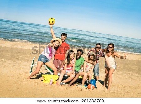Group of multiracial happy friends having fun with beach sport games - International concept of summer joy and multi ethnic friendship all together  - Sunny afternoon color tones with tilted horizon - stock photo