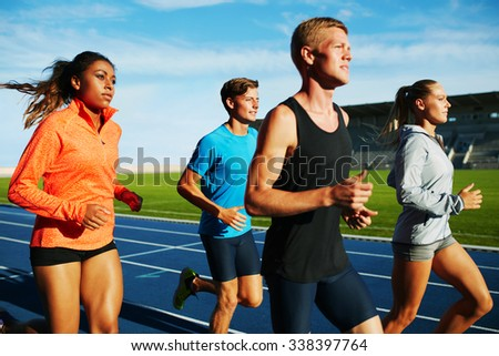 Group of multiracial professional athletes practicing running in stadium. Male and female athletes running together on racetrack. - stock photo