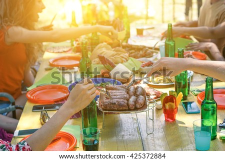 Group of multiracial students having barbecue on a sunny day - Young cheerful people eating meat on summer time - Concept about good and positive mood with friends - Focus on sausages - stock photo