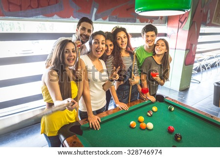 Group of multiracial young people standing next to pool table and taking a selfie - Students spending an evening at pub - stock photo