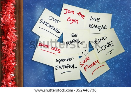 Group of New year Resolutions written on Post it Notes stack on window glass with Christmas tinsel on wooden frame - stock photo