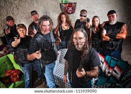 Group of nine biker gang members in leather jackets indoors