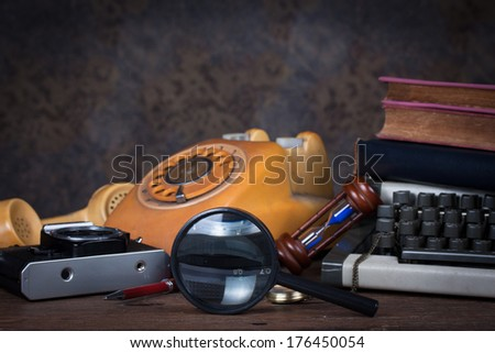 Group of objects on wood table. magnifying glass, old telephone, type writer, old camera, Still life - stock photo