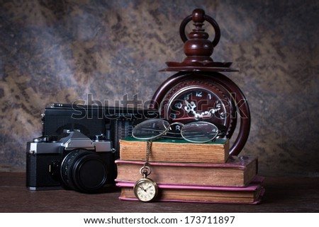 Group of objects on wood table.  wood clock, old watch, retro radio, camera, Still life