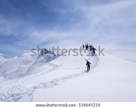 Group of off piste skiers walking on ridge. - stock photo