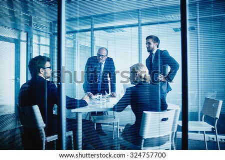 Group of office workers listening to their colleague at meeting - stock photo